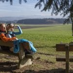 Wanderer machen Pause auf einer Bank mit schöner Aussicht